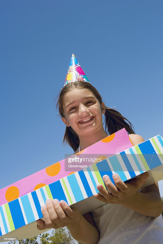 Portrait of a girl holding birthday presents and smiling : Foto de stock