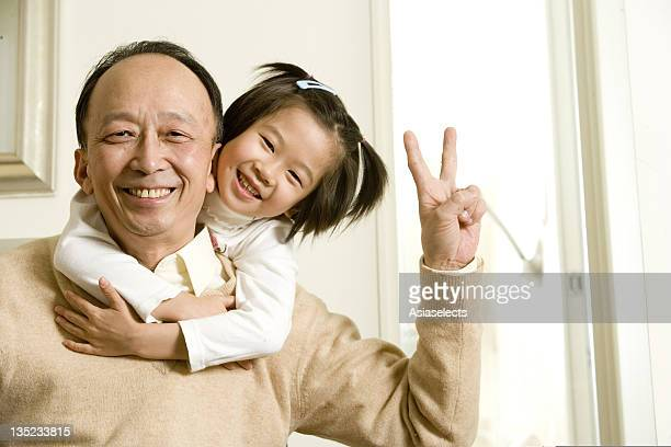Portrait of a girl hugging her grandfather, Shanghai, China