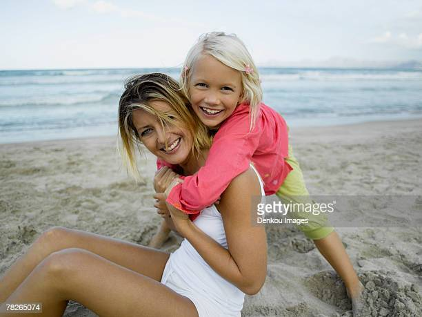 Portrait of a girl hugging her mother on the beach