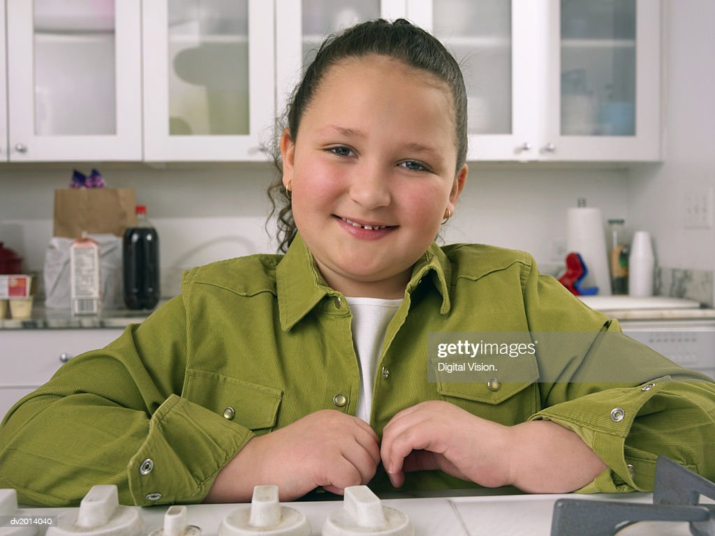 Portrait of a Girl in a Kitchen Wearing a Green Shirt : Stock Photo