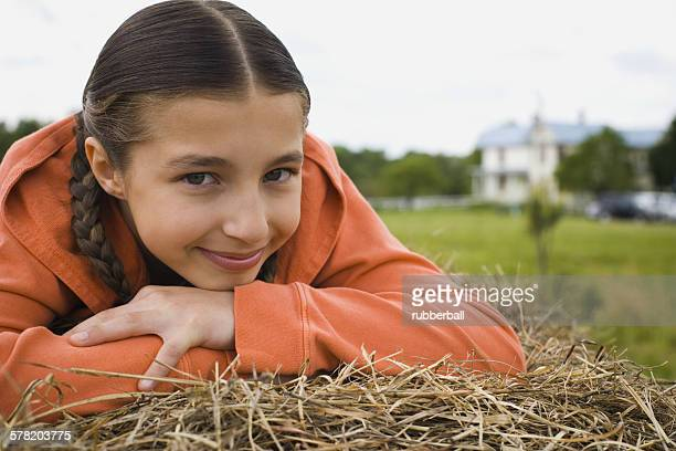 Portrait of a girl leaning over a haystack