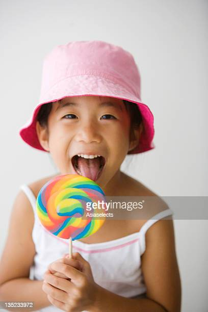 Portrait of a girl licking a lollipop
