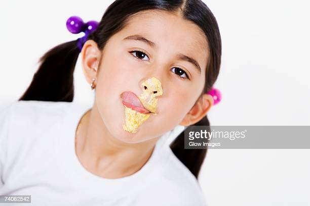 Portrait of a girl licking cream on her face