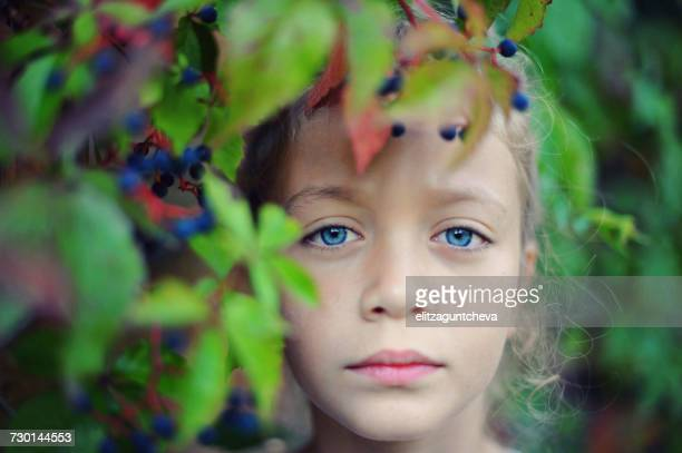 Portrait of a girl looking through leaves
