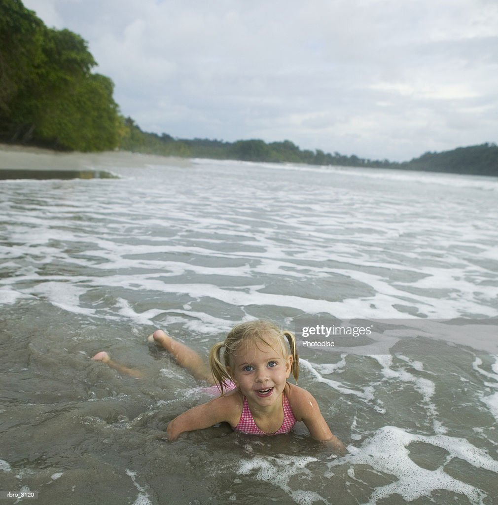 Portrait of a girl lying in water at the beach : Foto de stock