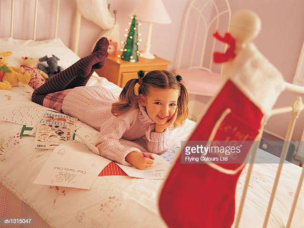 Portrait of a Girl Lying on a Bed Writing a Letter to Father Christmas