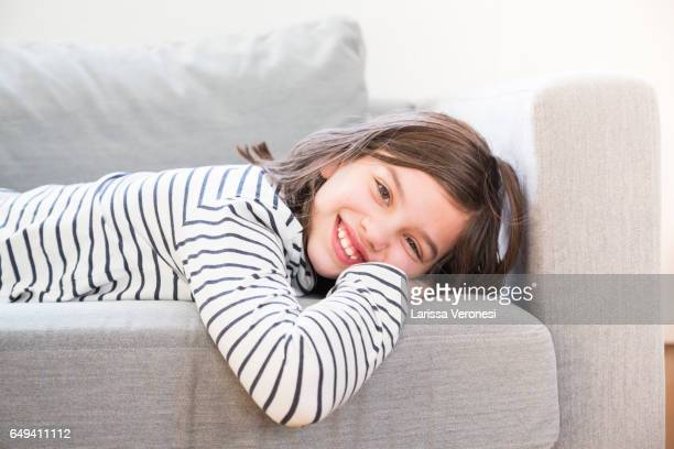 portrait of a girl lying on sofa - 10 11 jaar stockfoto's en -beelden