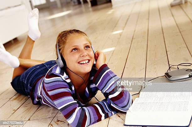 portrait of a girl (8-10) lying on the floor listening to music