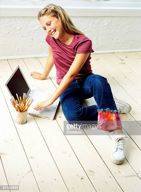 portrait of a girl (8-10) on the floor working on a laptop