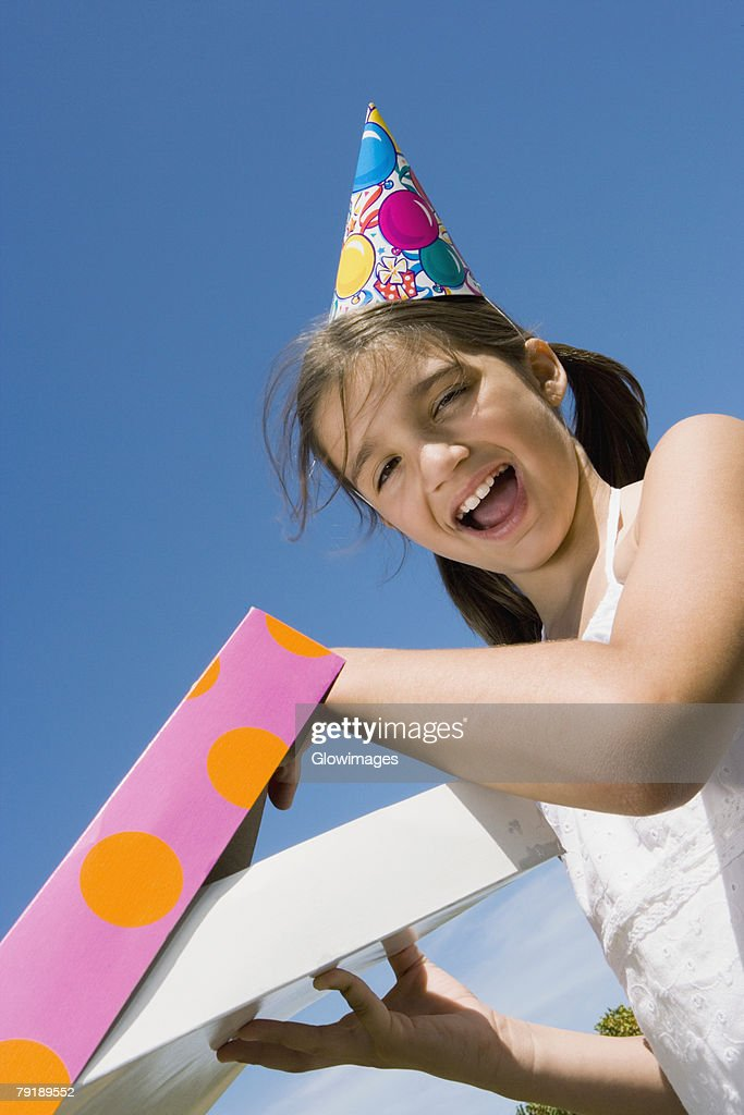 Portrait of a girl opening her birthday present and laughing : Foto de stock