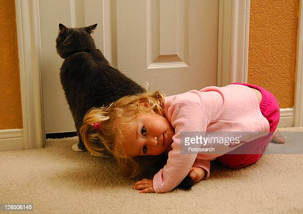 Portrait of a girl playing with a cat