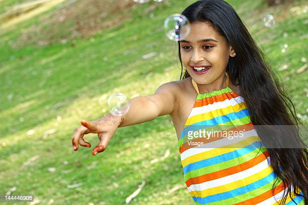 Portrait of a girl playing with bubbles