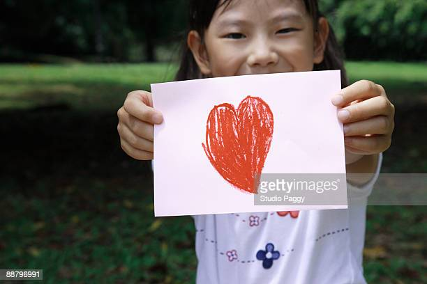 Portrait of a girl showing heart shape drawing on a sheet of paper