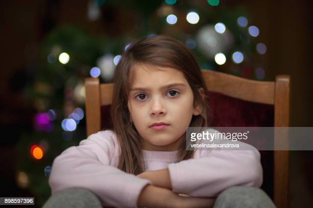 portrait of a girl sitting in front of a christmas tree with her arms folded - sulking stock pictures, royalty-free photos & images