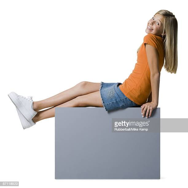 Portrait of a girl sitting on a blank sign