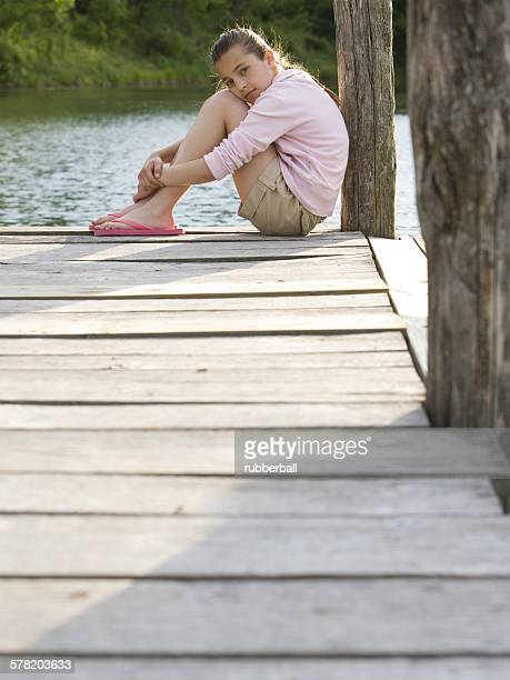 portrait of a girl sitting on a pier - 10 11 years stock photos and pictures