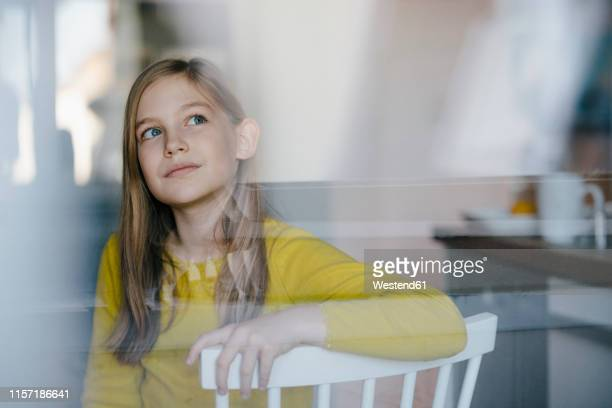 portrait of a girl sitting on chair at home looking up - nur kinder stock-fotos und bilder