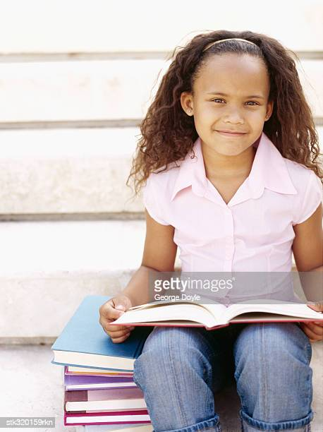 portrait of a girl sitting on stairs and reading a book