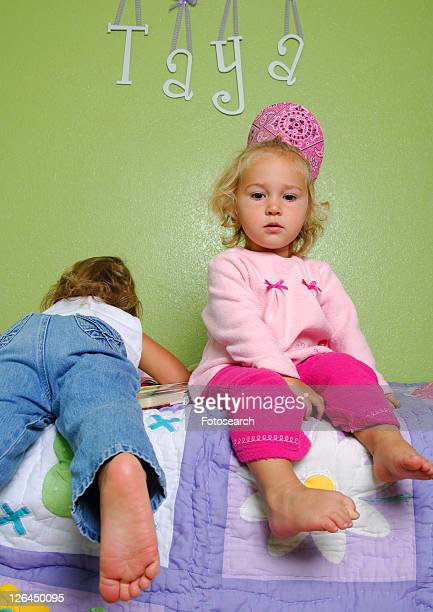 portrait of a girl sitting on the bed with her sister lying on the bed beside her - little girls bare bum stock pictures, royalty-free photos & images