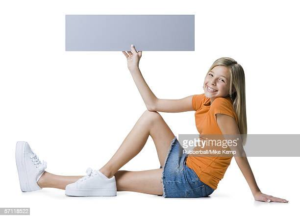 portrait of a girl sitting on the floor and holding a blank sign - little girls up skirt fotografías e imágenes de stock