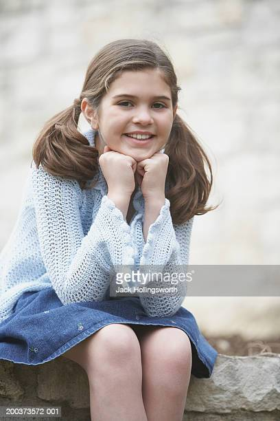 portrait of a girl sitting with her hands under her chin - under the skirt stock photos and pictures