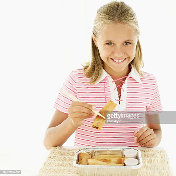portrait of a girl smiling and picking up spring rolls with chopsticks