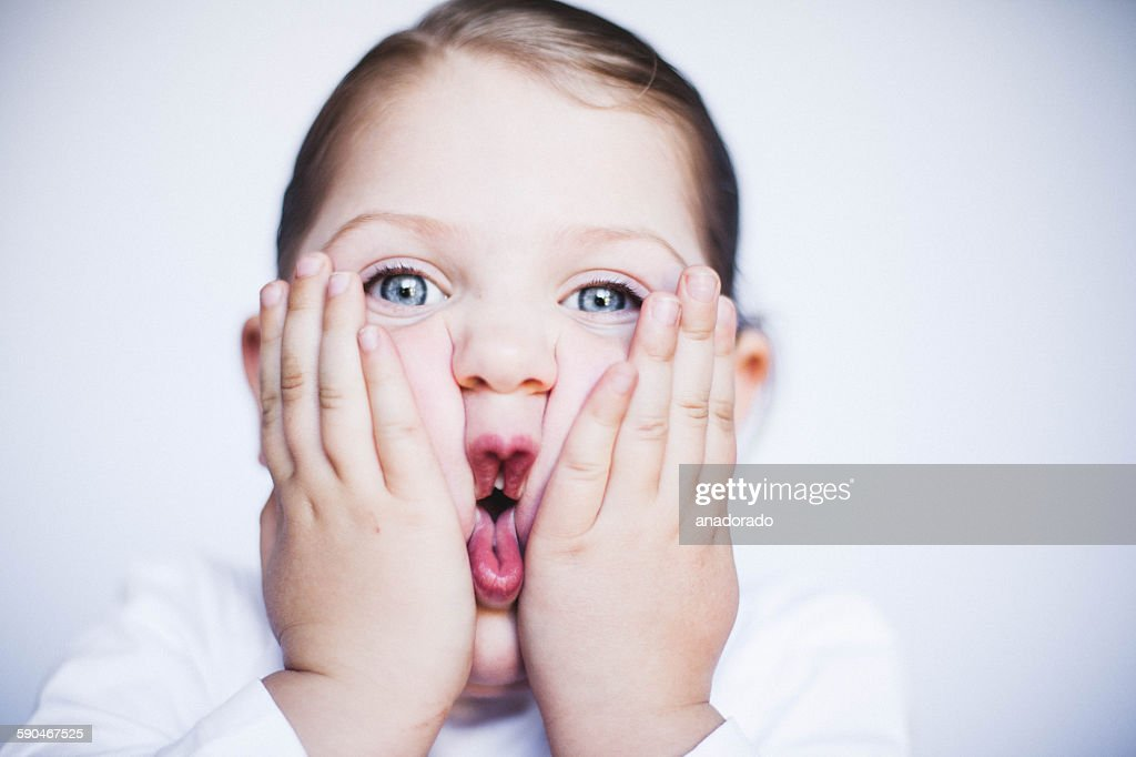 Portrait of a girl squashing her cheeks together making a funny face
