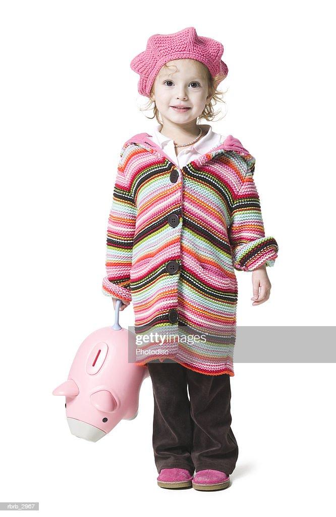 Portrait of a girl standing holding a piggybank : Foto de stock