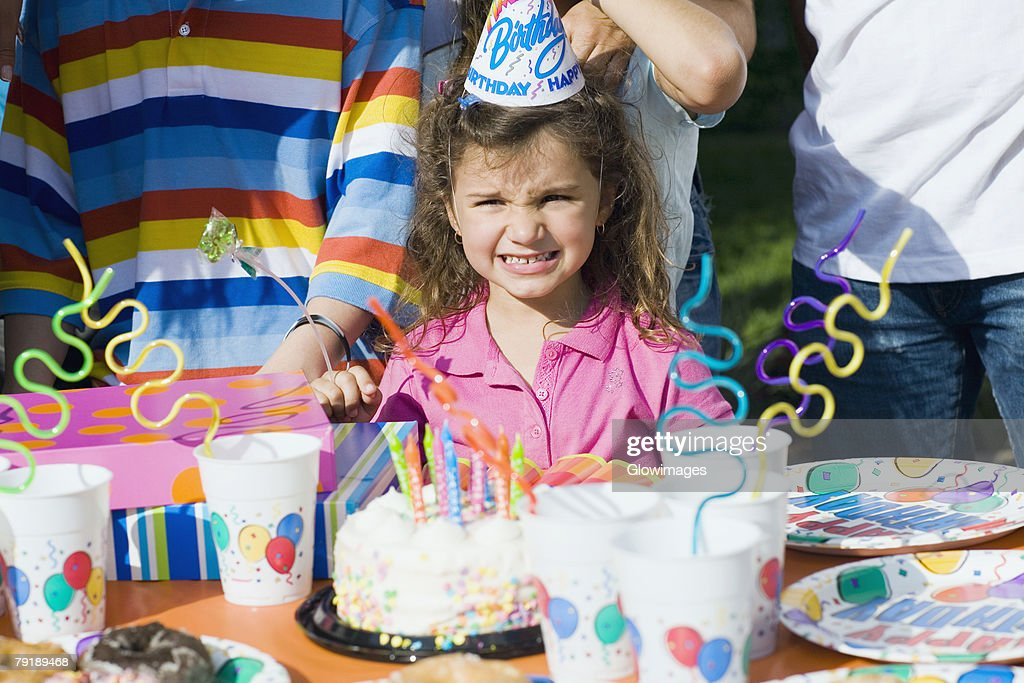 Portrait of a girl standing in front of a birthday cake : Foto de stock