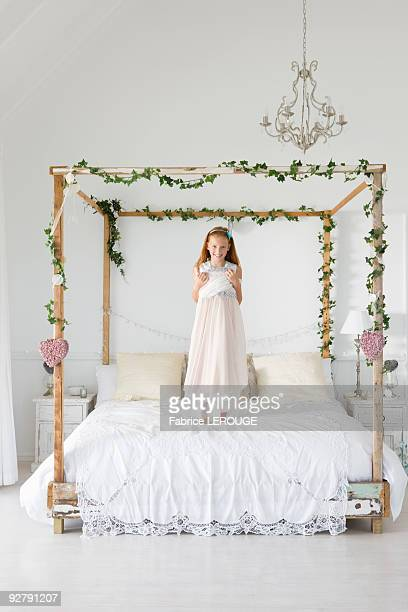 Portrait of a girl standing on the bed