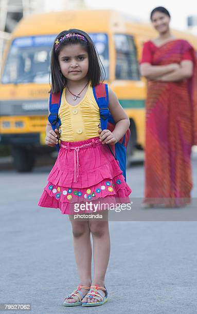 Portrait of a girl standing on the road with her teacher standing in the background