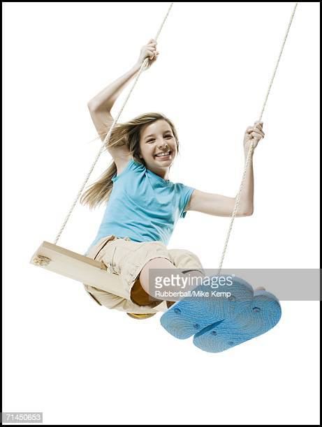 Portrait of a girl swinging on a rope swing