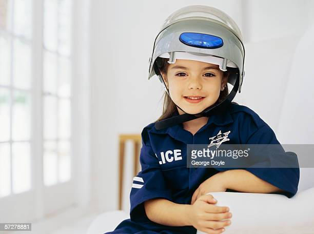 Portrait of a girl wearing a helmet and pretending to be a policewoman