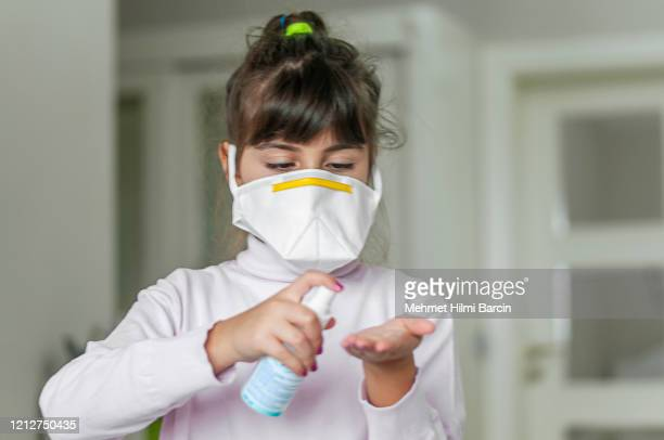 portrait of a girl wearing a protective mask with hand sanitizer - respirator mask stock pictures, royalty-free photos & images