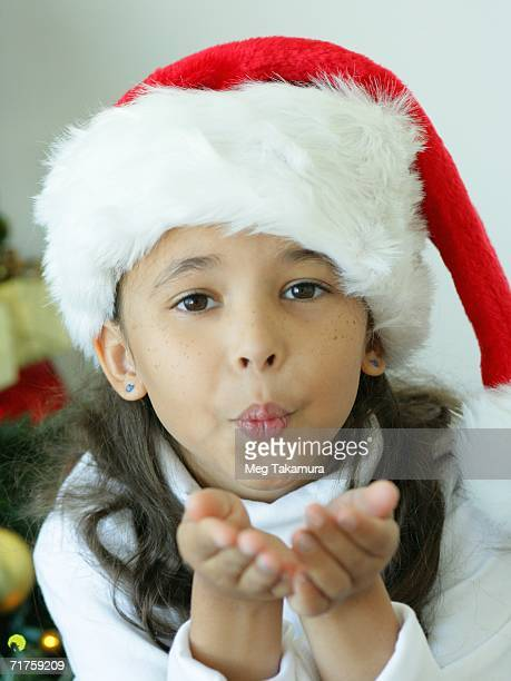 portrait of a girl wearing a santa hat and blowing a kiss - indian girl kissing stock photos and pictures
