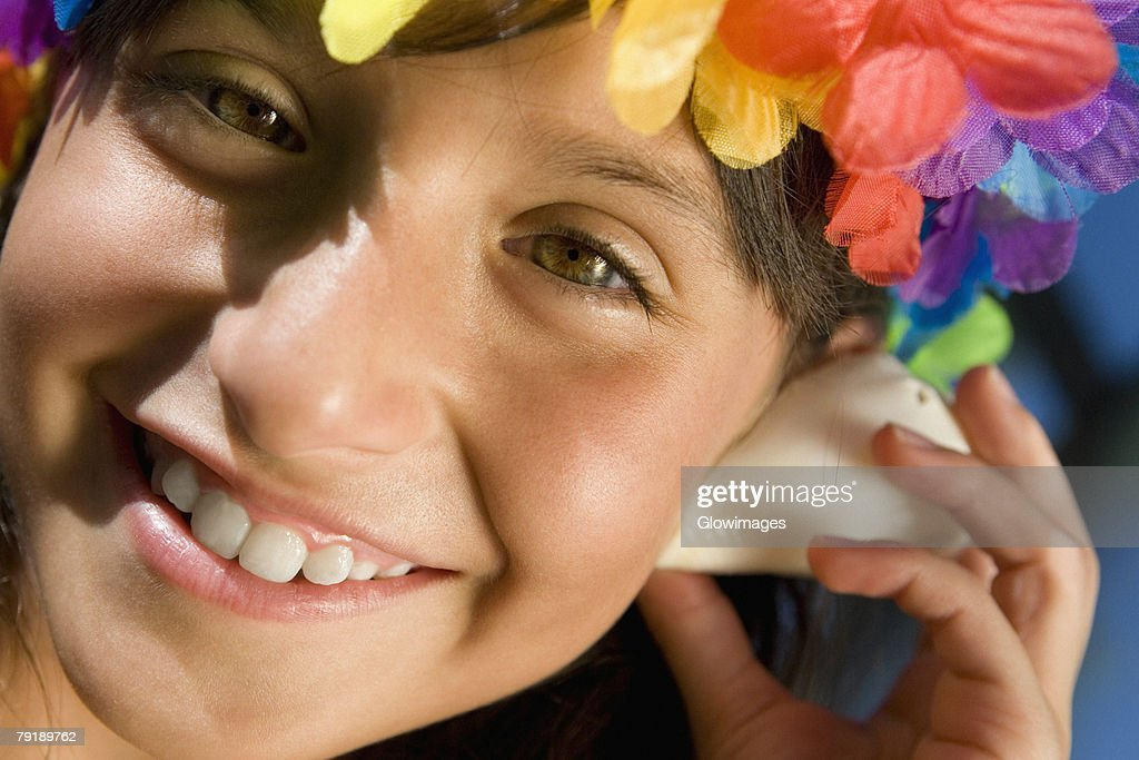 Portrait of a girl wearing flowers and listening to a conch shell : Stock Photo