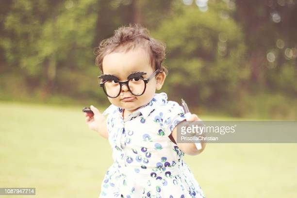 portrait of a girl wearing novelty glasses with a moustache drawn on her face - novelty item stock pictures, royalty-free photos & images