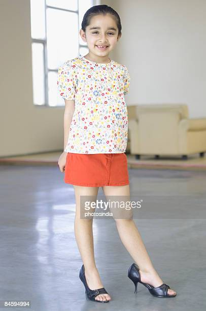 portrait of a girl wearing oversize high heels - little girl in high heels stock photos and pictures