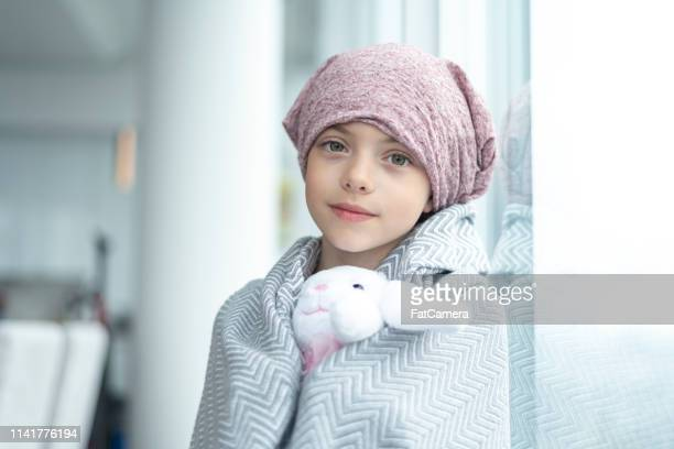 portrait of a girl with cancer holding a stuffed toy - cancer illness stock pictures, royalty-free photos & images