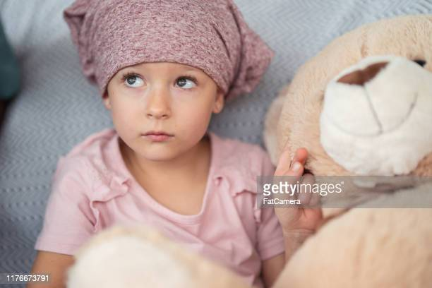 portrait of a girl with cancer holding a stuffed toy - leukemia stock pictures, royalty-free photos & images