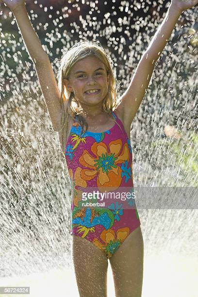 Portrait of a girl with her hands raised in a spray of water