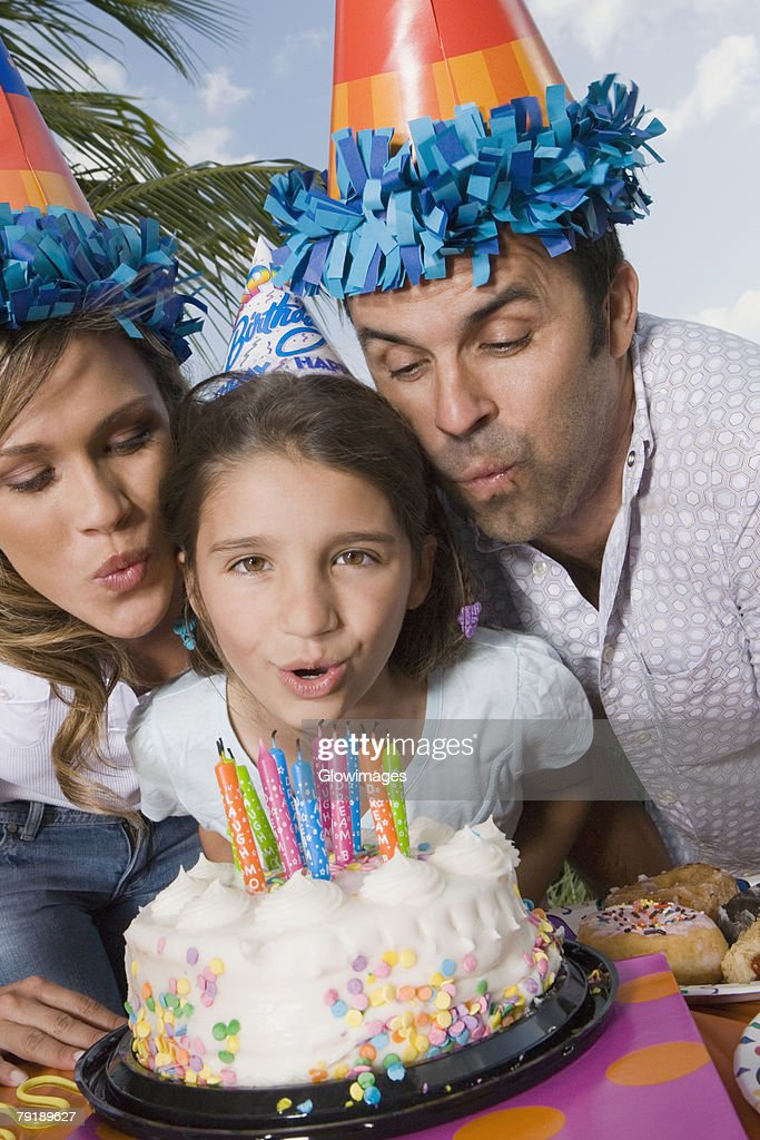 Portrait of a girl with her parents blowing candles on a birthday cake : Foto de stock