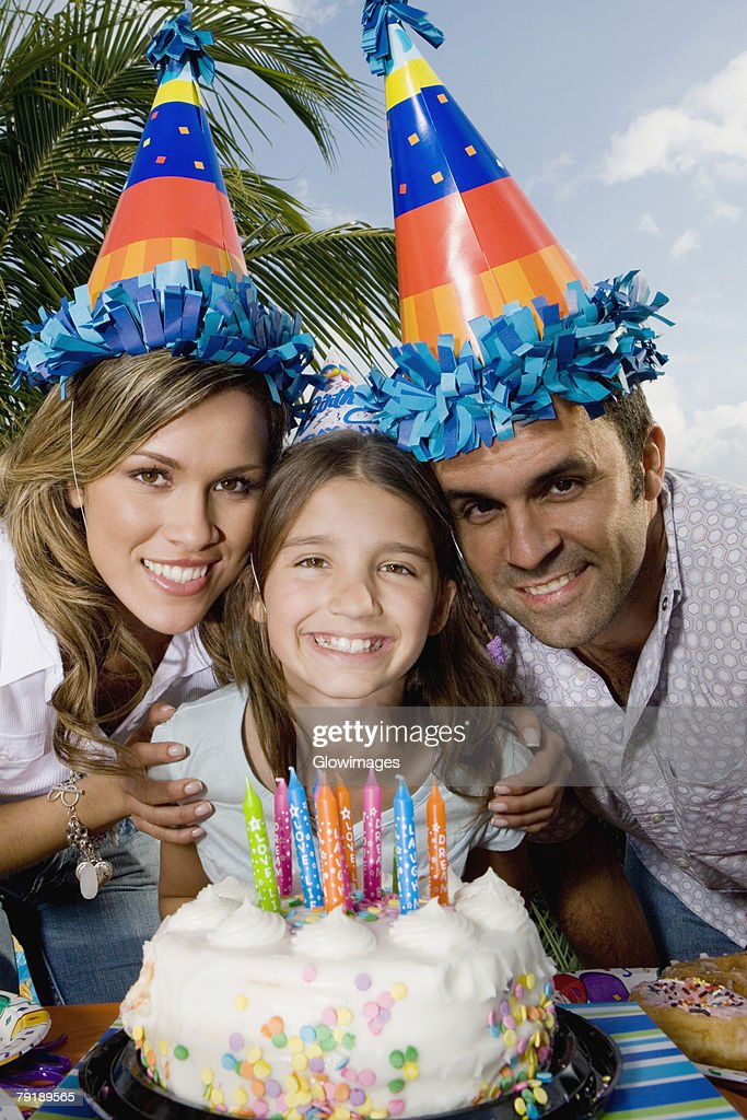 Portrait of a girl with her parents standing in front of a birthday cake and smiling : Foto de stock
