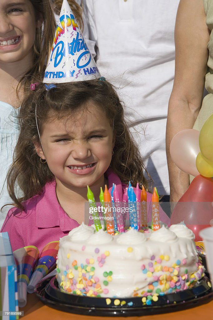 Portrait of a girl with her sisters standing in front of a birthday cake : Stock Photo