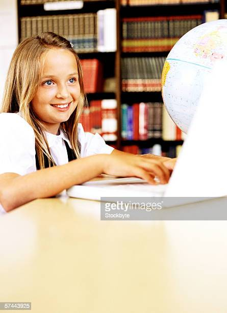 portrait of a girl (8-10) working on a laptop in the library - 10 11 jahre stock-fotos und bilder