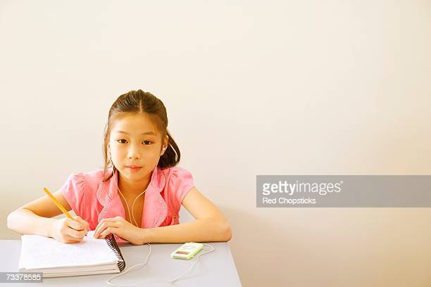 Portrait of a girl writing in a spiral notebook and listening to an MP3 player