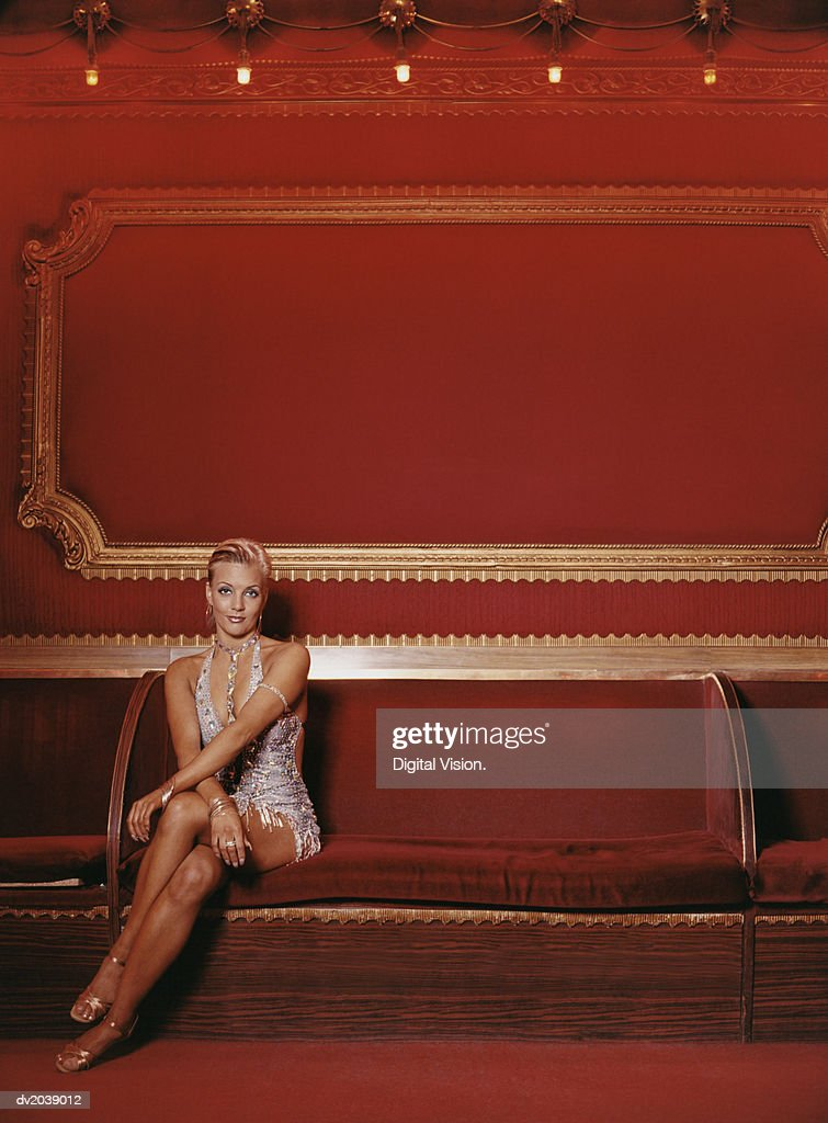 Portrait of a Glamorous Woman Sitting on a Red Seat : Stock Photo