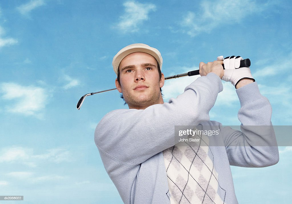 Portrait of a Golfer Swinging a Golf Club : Stock Photo