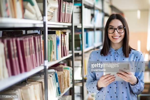 ritratto di uno splendido studente che usa un tablet in una libreria - libreria foto e immagini stock