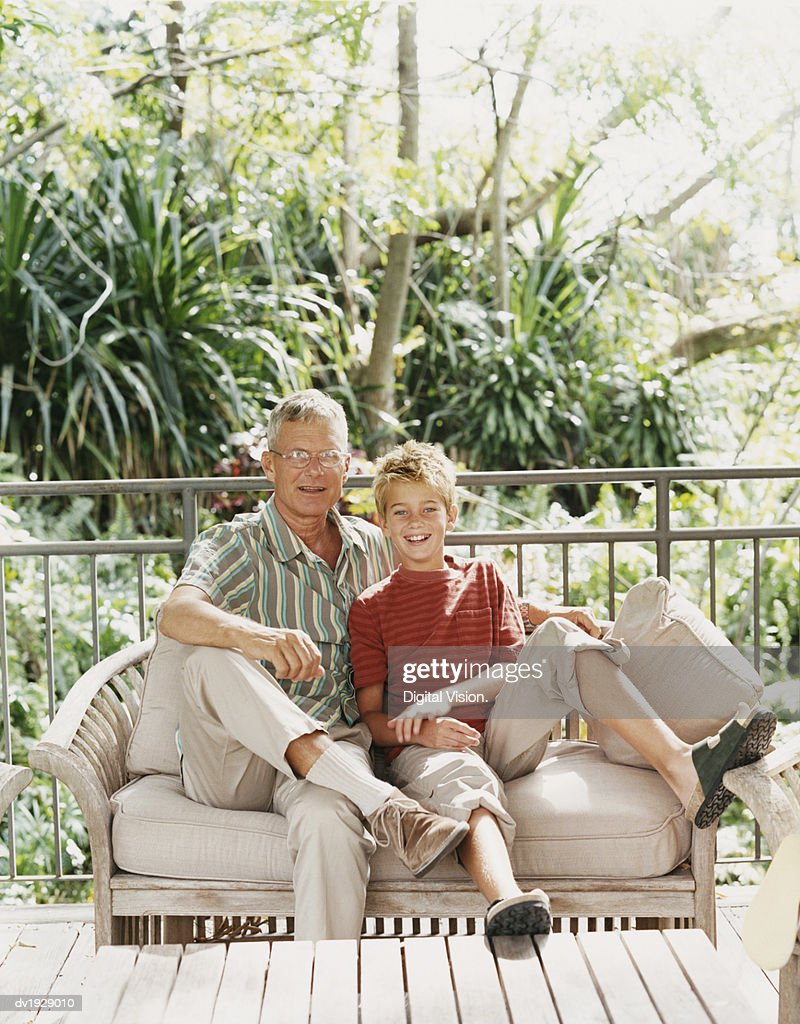 Portrait of a Grandfather and Grandson Sitting on a Bench : Stock Photo
